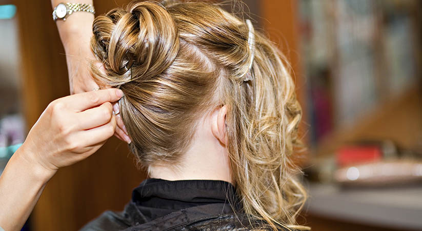 Woman having her hair styled in an formal updo.